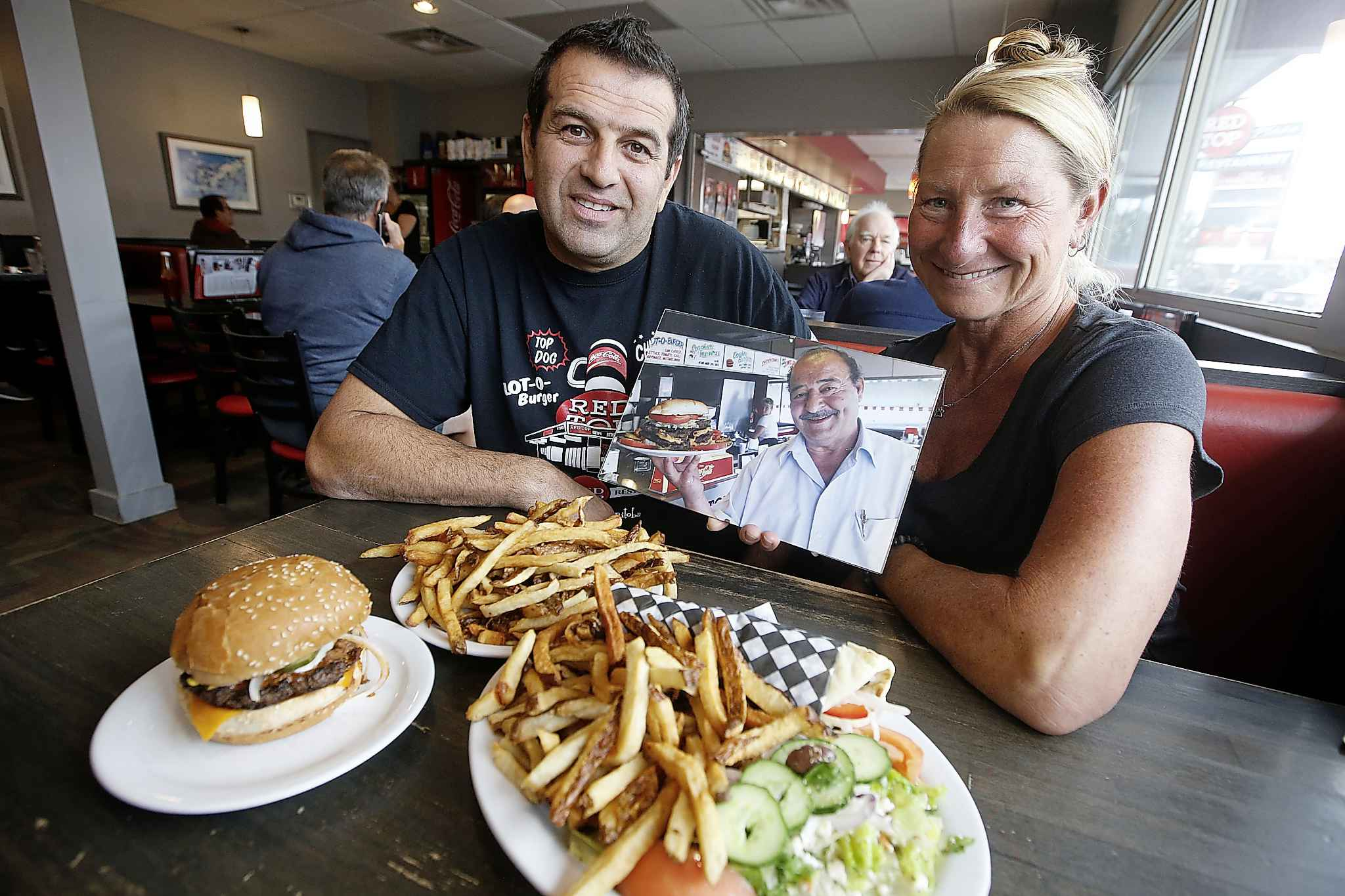 Stavros Athanasiadis, owner, and Evelyn Campbell, employee for 37 years, hold a photo of the original owner. (John Woods / Winnipeg Free Press)