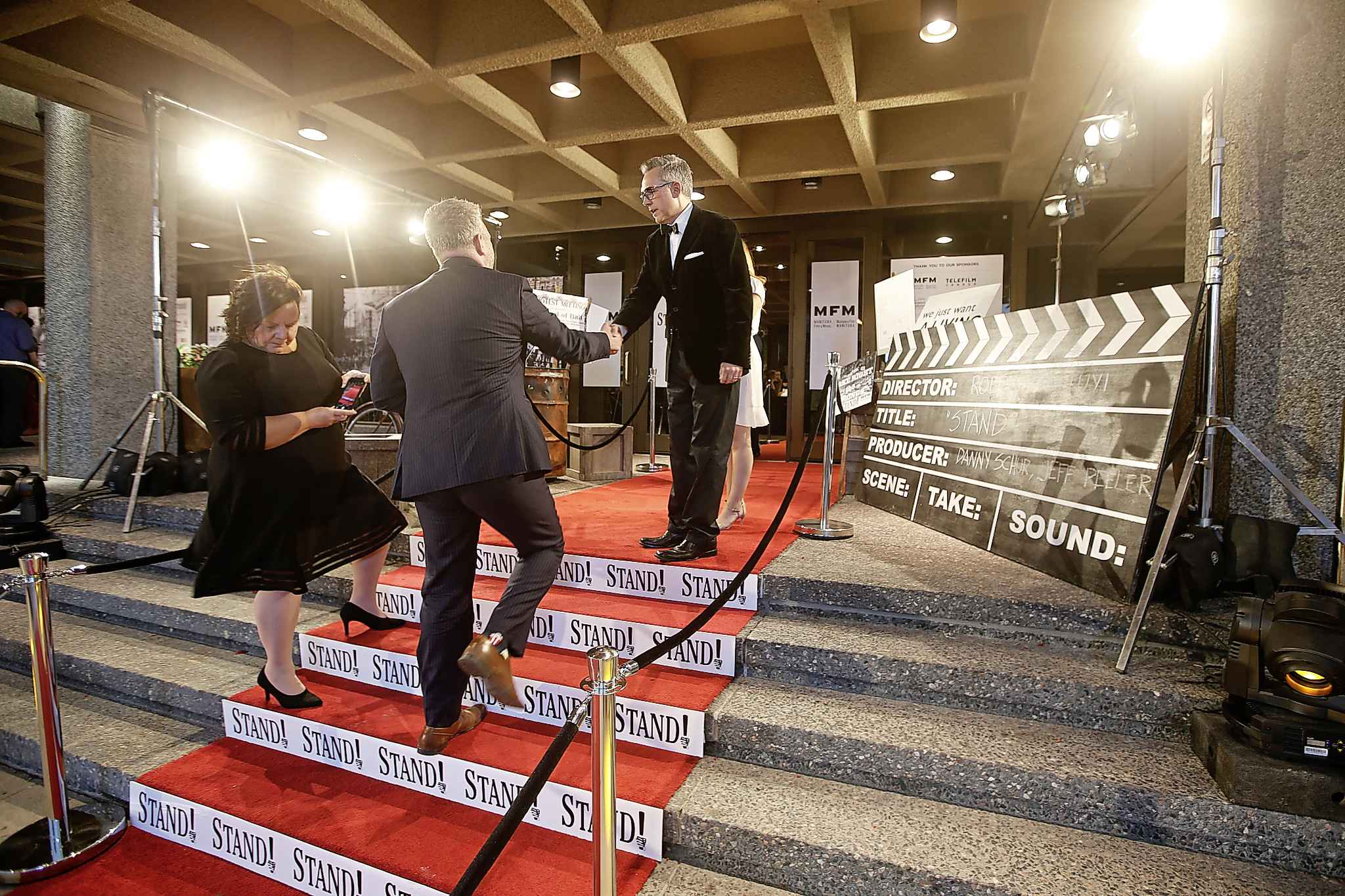 Producer Jeff Peeler welcomes a guest on the red carpet at the premiére of Stand! at the Centennial Concert Hall in Winnipeg on Tuesday. (John Woods / Winnipeg Free Press)