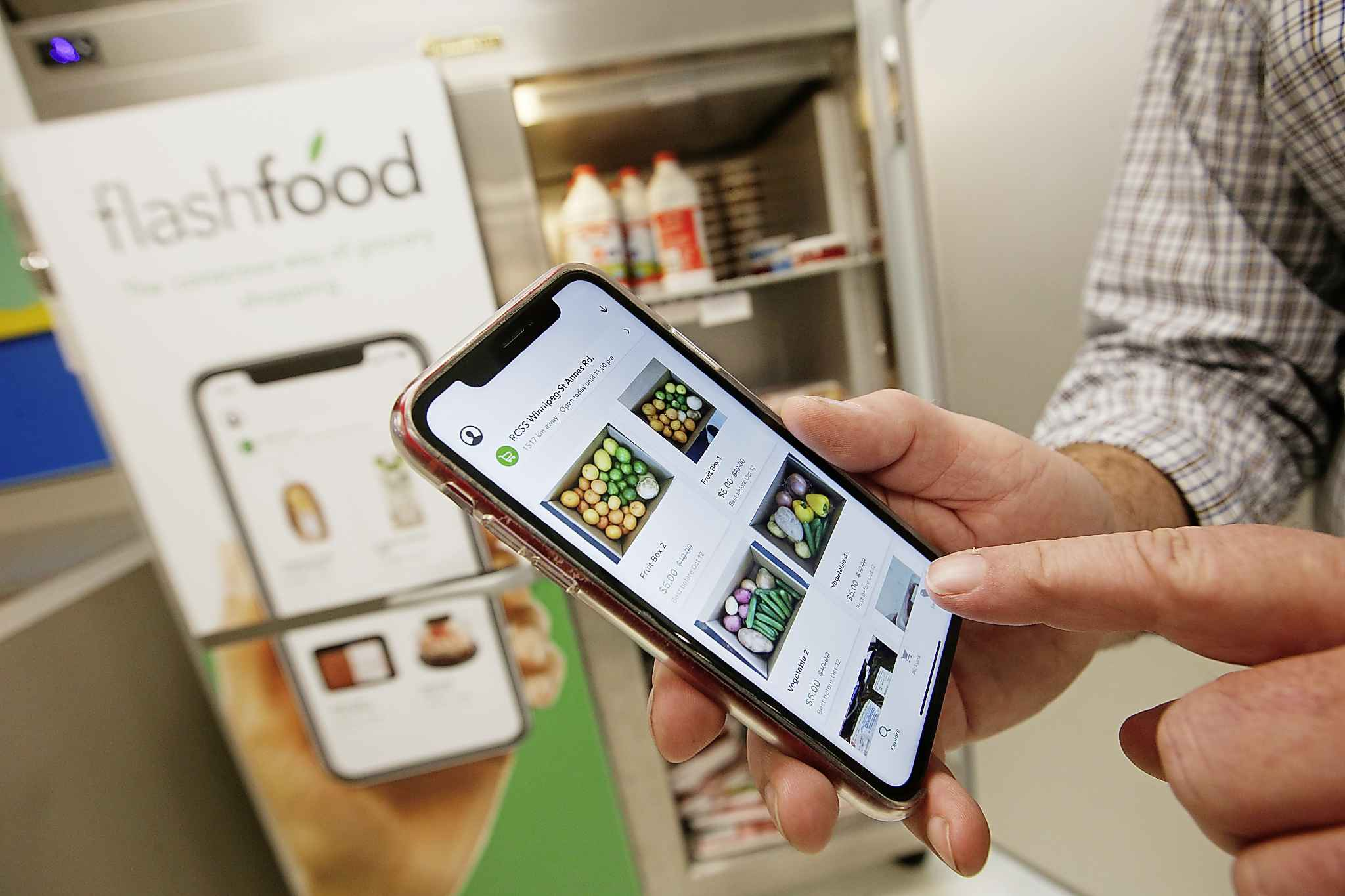 John Davidson, store manager at the Superstore on St Anne's Road, shows off their new app, FlashFood, which allows buyers to purchase near expired food at reduced prices. (John Woods / Winnipeg Free Press)