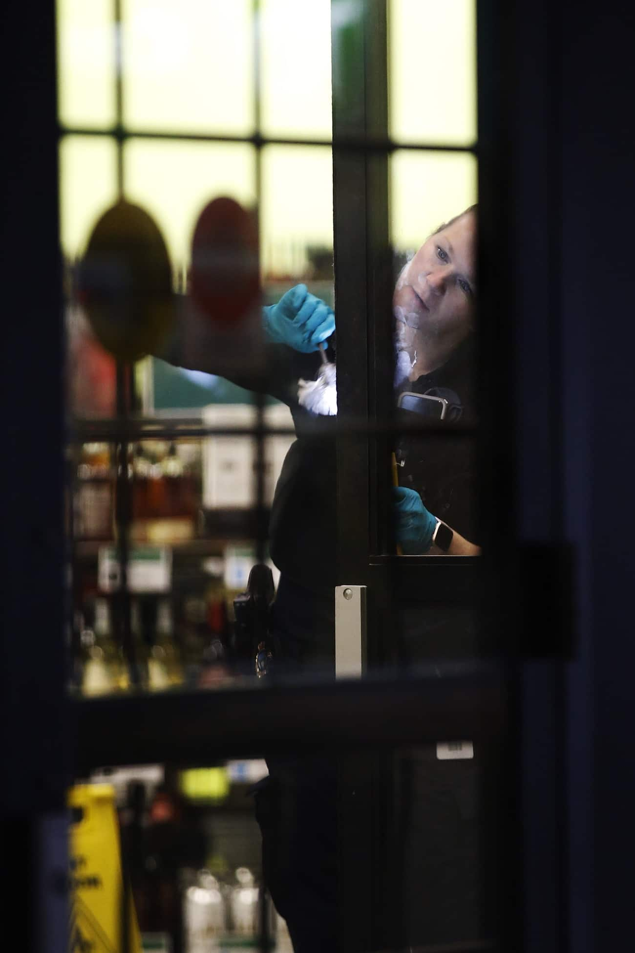 Police dusts for prints as they investigate a robbery at a Liquor Mart on Keewatin in Winnipeg on November 20, 2019. An employee was injured in the robbery. (John Woods / Canadian Press files)