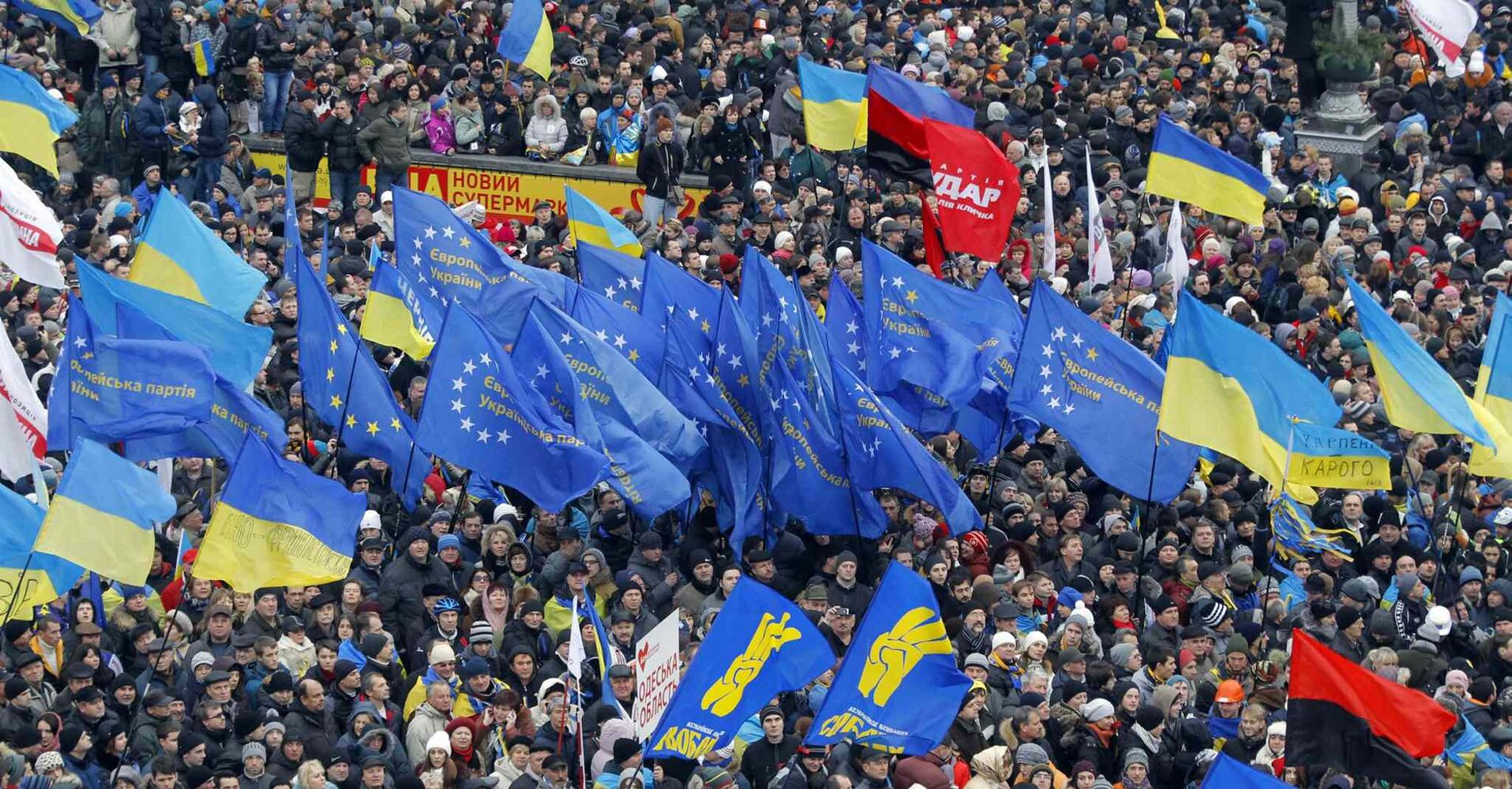 Demonstrators wave flags as they gather during a rally in downtown Kiev, Ukraine, on Sunday. As many as 100,000 demonstrators chased away police to rally in the center of Ukraine's capital on Sunday, defying a government ban on protests on Independence Square, in the biggest show of anger over the president's refusal to sign an agreement with the European Union.  (CP)