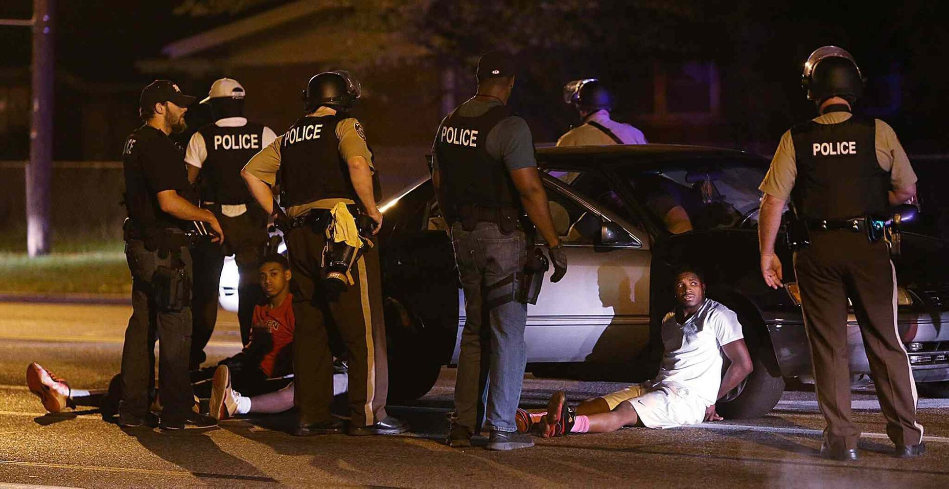 Police search the vehicle of three men they believed may have been involved in an assault on a man with a dog. Two of the vehicle's occupants were arrested and one was released.  (Chris Lee / St. Louis Post-Dispatch)