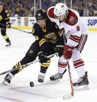 Arizona Coyotes' Tobias Rieder (8) and Boston Bruins' David Pastrnak battle for the puck during the second period of an NHL hockey game in Boston Saturday, Feb. 28, 2015. (AP Photo/Winslow Townson)