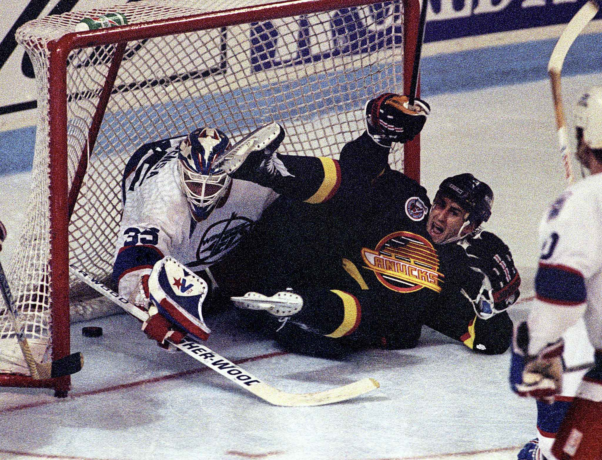 Vancouver forward Greg Adams slides into Jets goalie Bob Essensa knocking the puck into the net in overtime, scoring the series-winning goal and effectively ending the Jets' season.