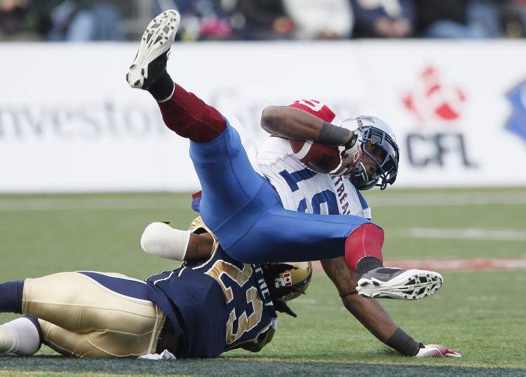 Winnipeg Blue Bombers' Jonathan Hefney (23) tackles Montreal Alouettes' S.J. Green (19) during the first half of their CFL game in Winnipeg on Saturday. (John Woods / The Canadian Press)