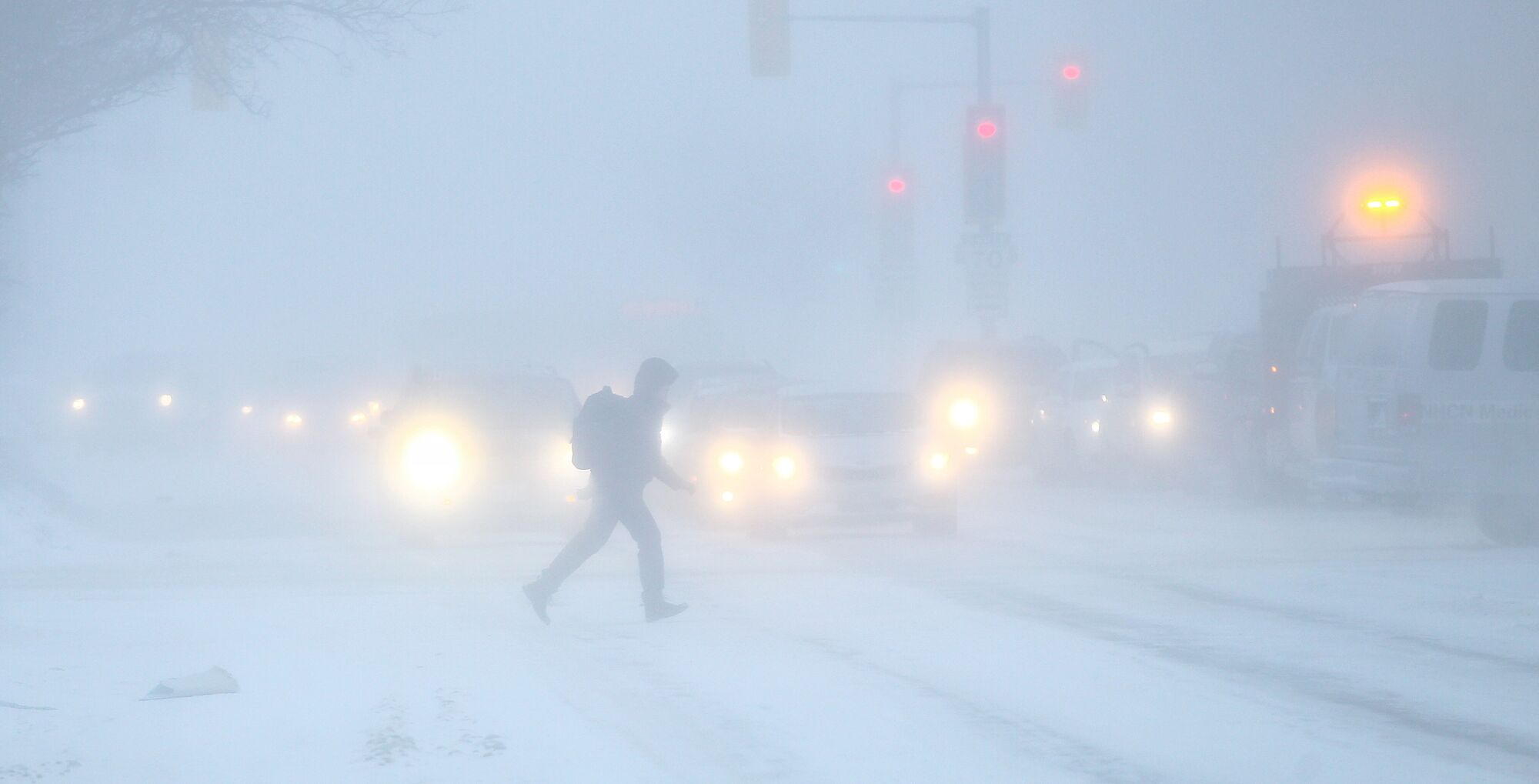 A pedestrian dashes across Portage Avenue at Maryland Street Thursday morning as high winds cause blowing snow.</p>