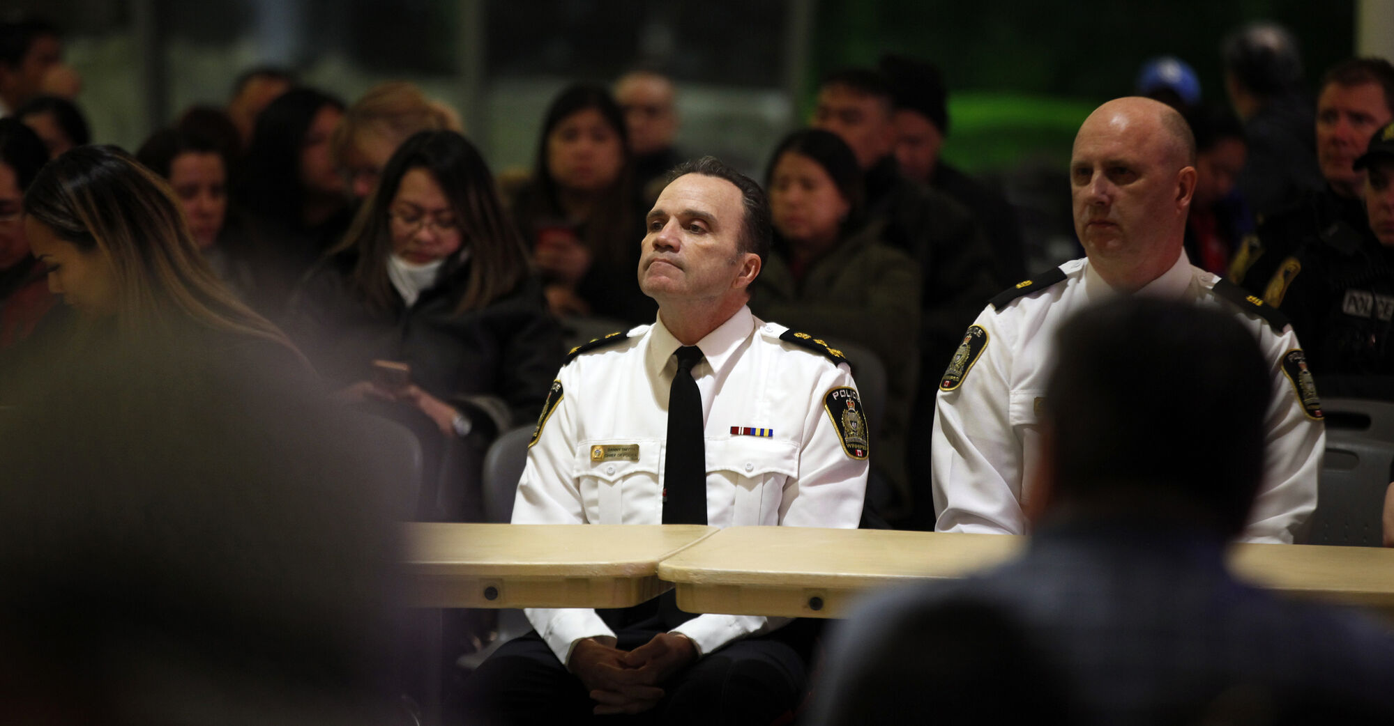 Police Chief Danny Smyth waits his turn to address a crowd gathered at the Maples Collegiate on March 8.