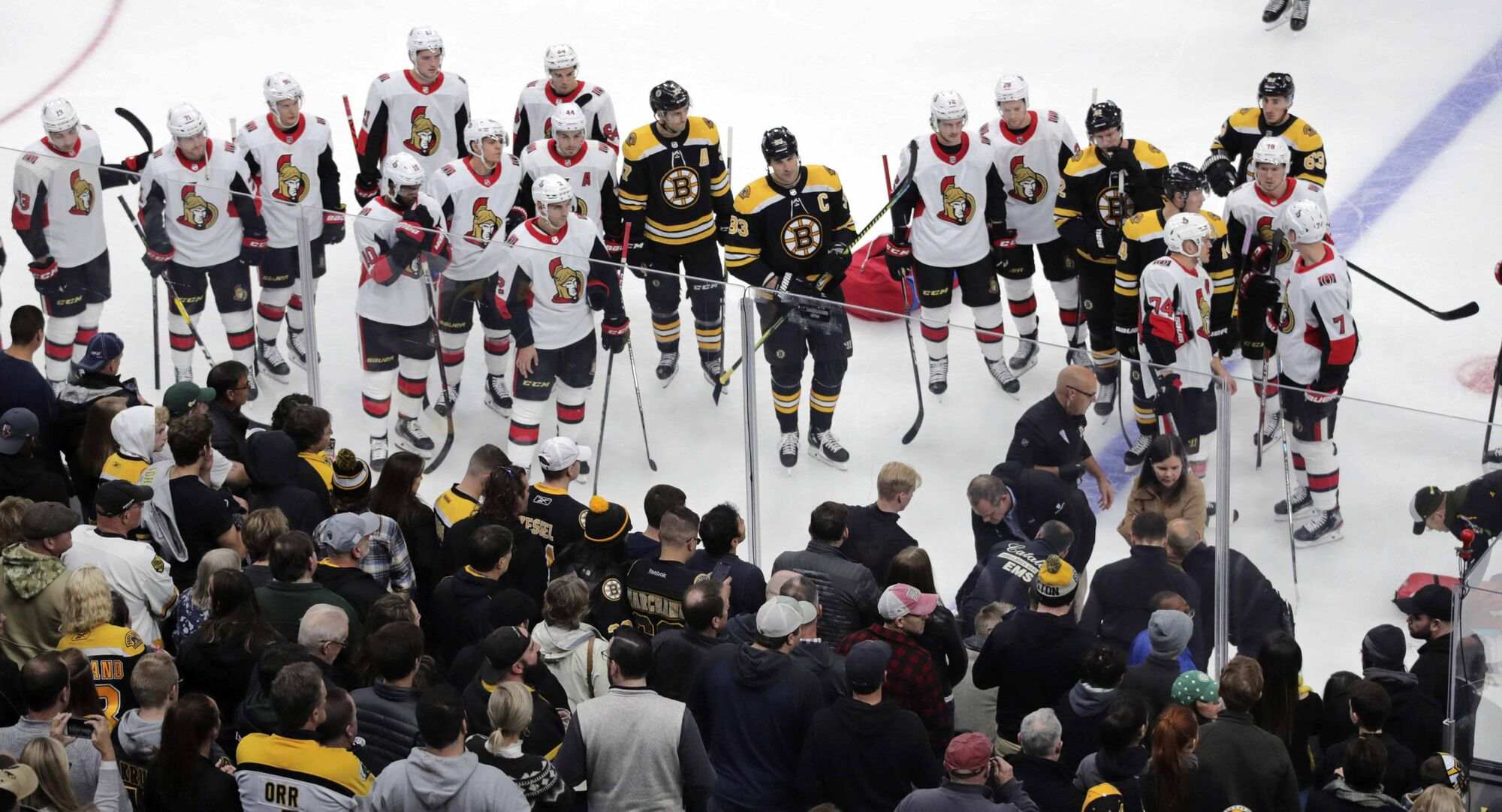 Ottawa Senators and Boston Bruins players watch as medical workers attend to Scott Sabourin, who was injured on a play with David Backes during the first period Saturday ion Boston. (Charles Krupa /  Asspociated Press files)