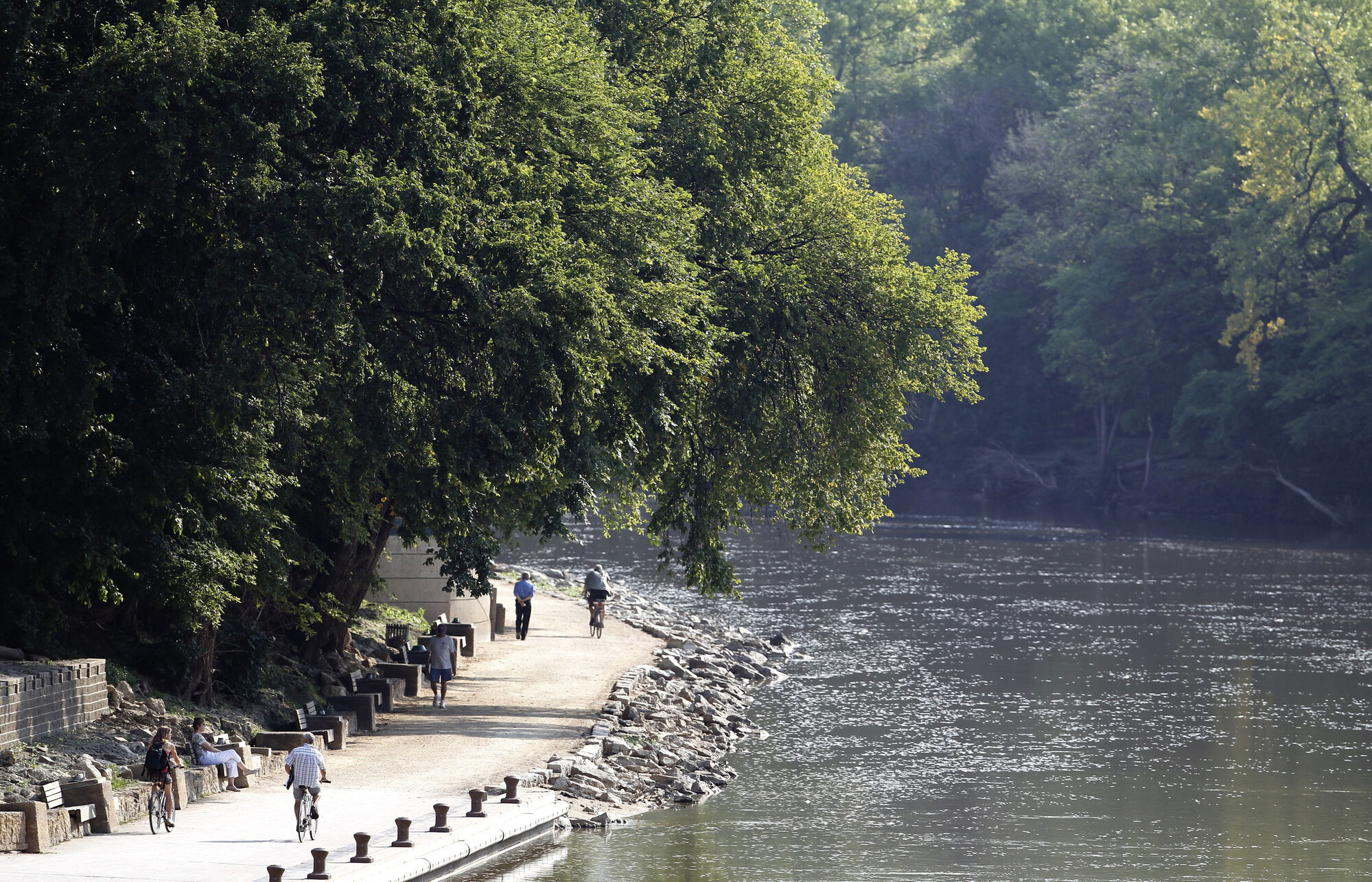 People walking and riding along the river walk that follows the Assiniboine River near the Legislative Building, Sunday, August 25, 2013. (TREVOR HAGAN/WINNIPEG FREE PRESS)