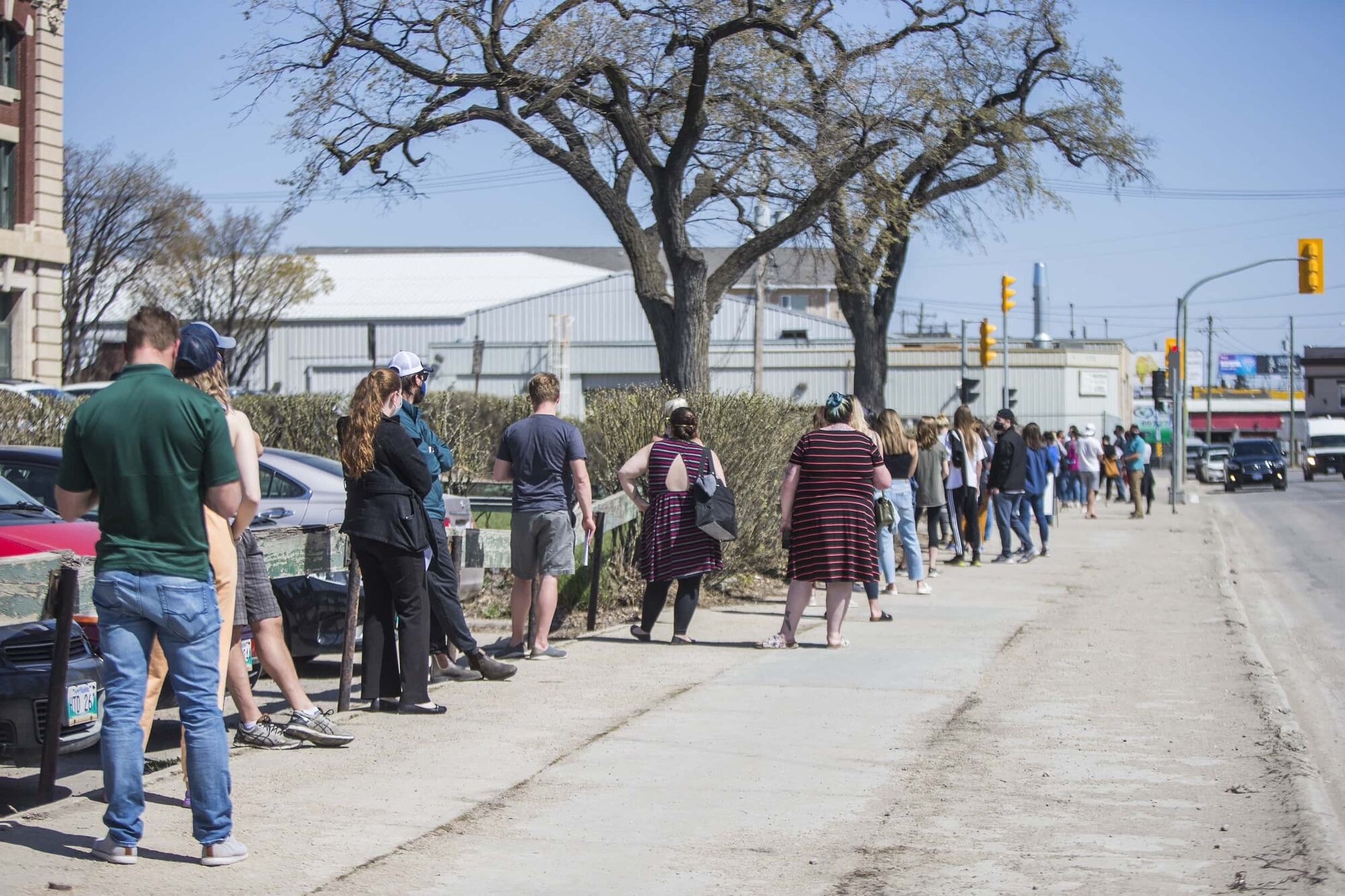 A mid-May line-up snakes down the sidewalk at a COVID-19 vaccine clinic. (Mikaela MacKenzie / Winnipeg Free Press files)