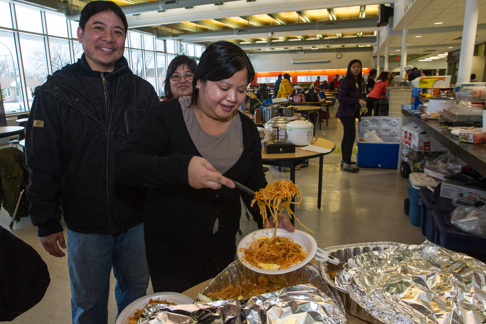 Liz Leung serves up a traditional dish of palabok during the all-day event at Garden City Collegiate. On the menu: pancit, grilled pork chops with rice along with lumpia, empanadas and ginataan.