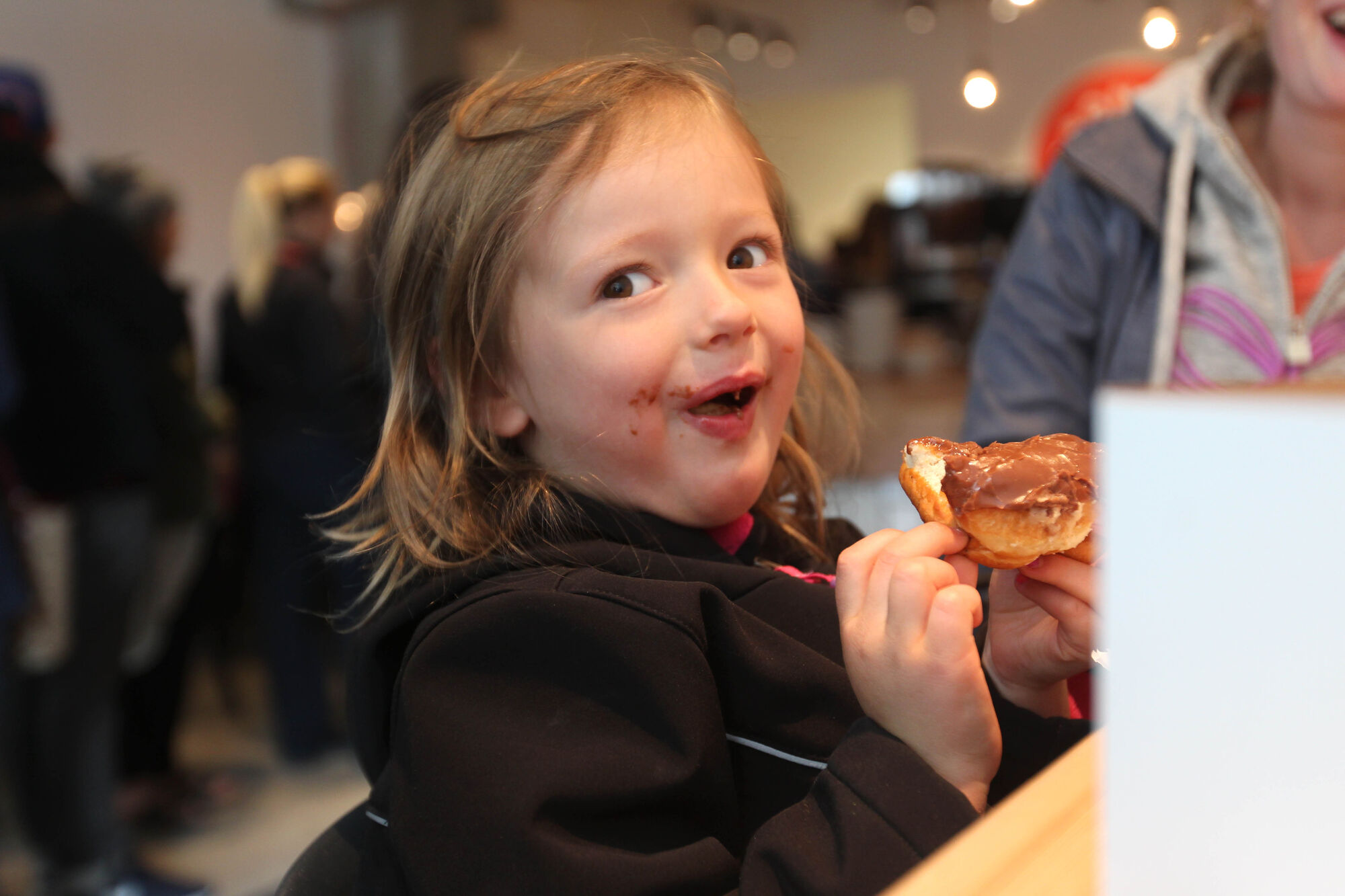 Four-year-old Myah Graham chomps into a Nutella Chocolate doughut on a recent Saturday morning visit with family.