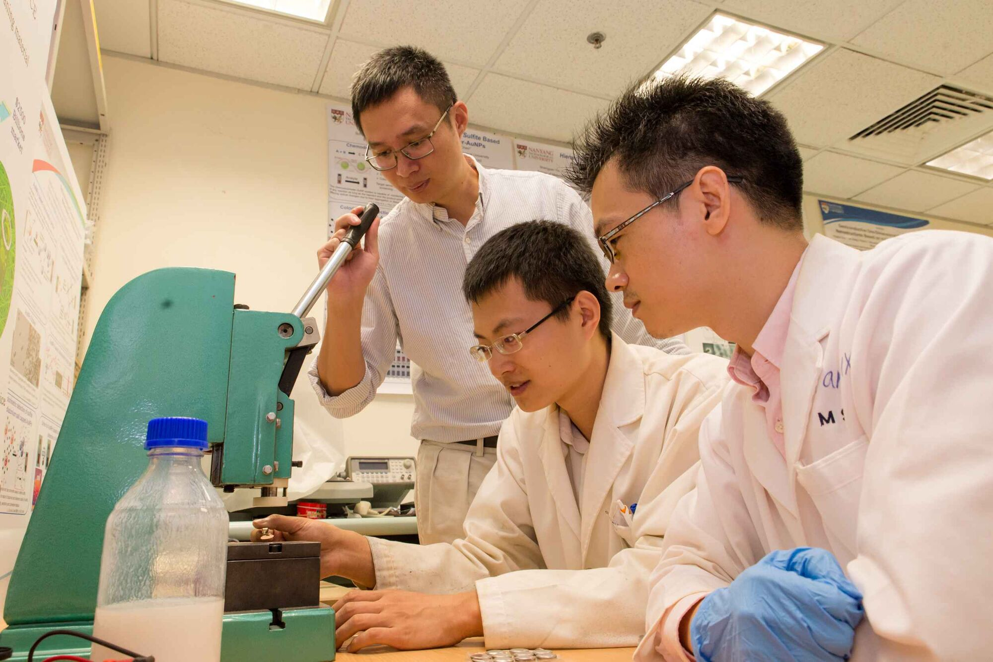 Prof. Chen Xiaodong (from left) supervises research fellow Tang Yuxin and PhD student Deng Jiyang in the making of a rechargeable battery.