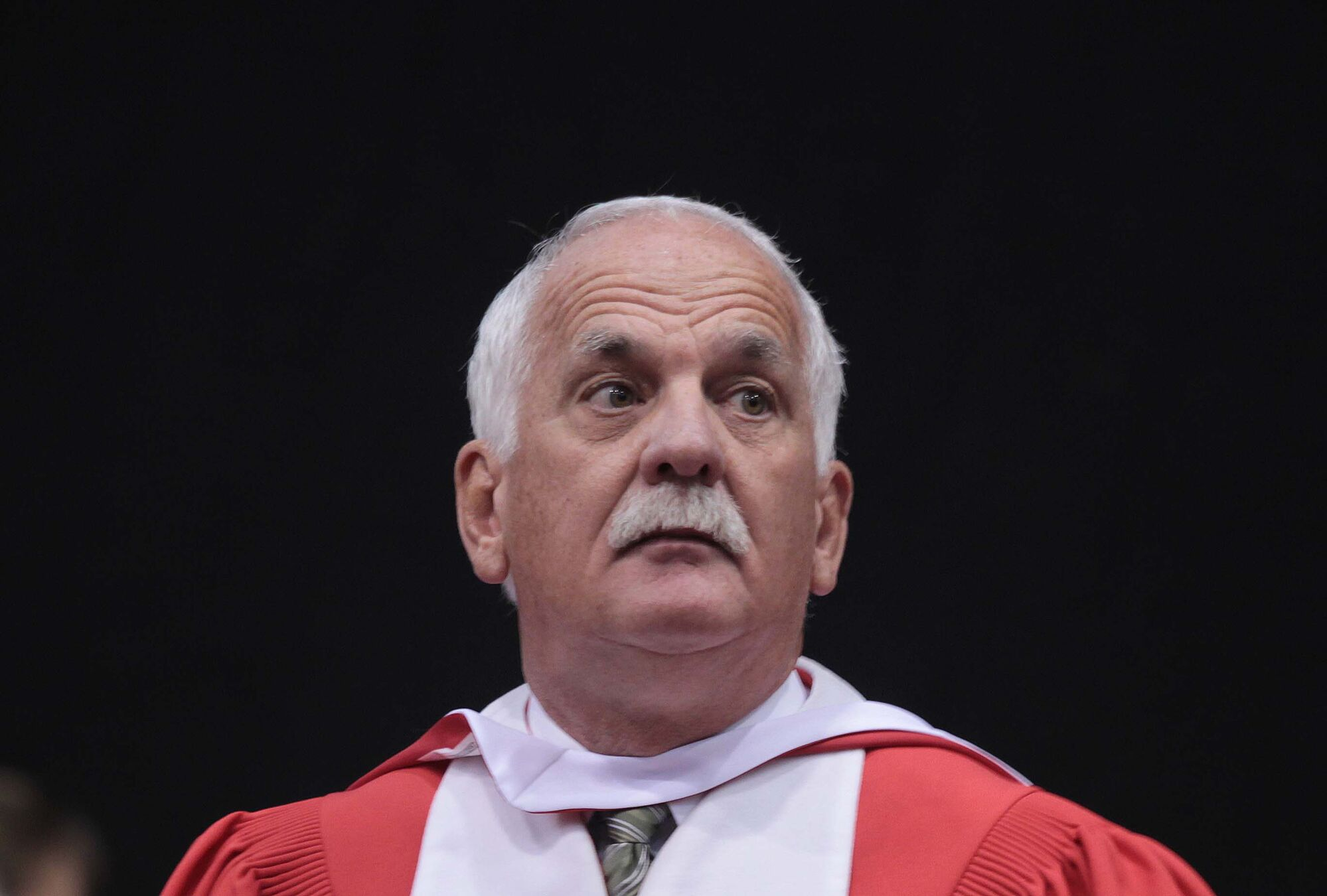 Vic Toews listens during the ceremony at U of W on Sunday.