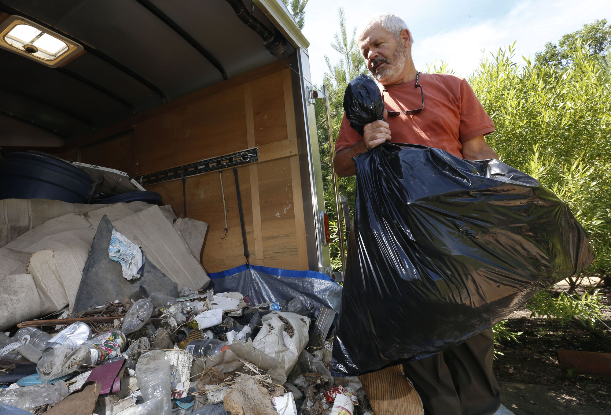 Bill Fisher with some of the trash recently collected along the Perimeter Highway near Brady Road. He will haul it to the dump.