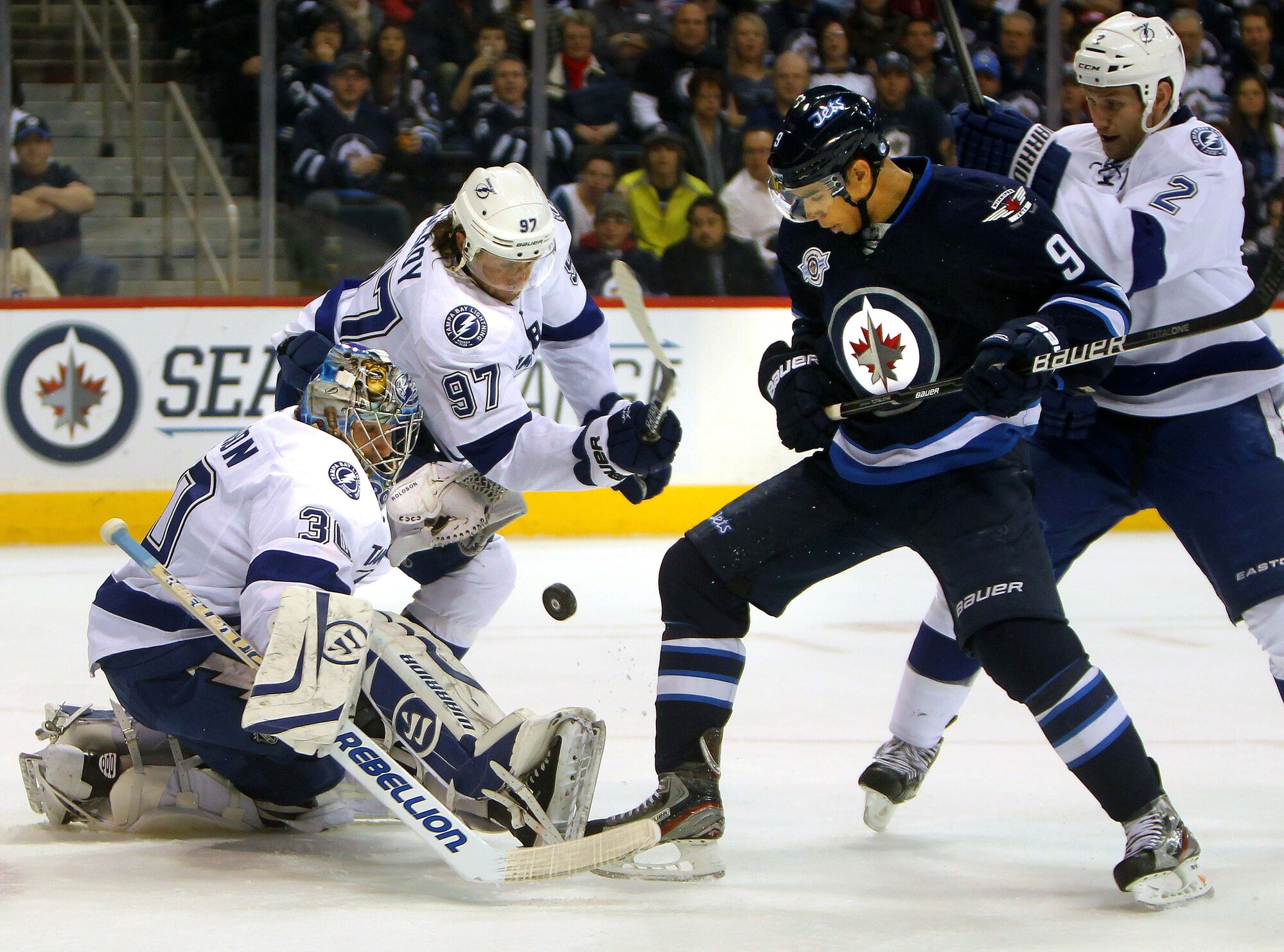 Tampa Bay Lightning goalie Dwayne Robinson keeps and eye on a bouncing puck with teammate Matt Gilroy while Winnipeg Jet Evander Kane and Florida's Eric Brewer fight for position Thursday.