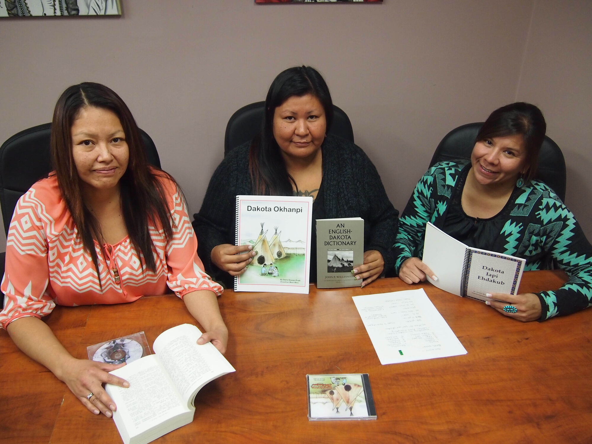 Carol Johnson, Donna Elk and Jennifer Bone of Sioux Valley Dakota Nation hold up some of the Dakota language resource materials being used to help other members learn the language during classes being held on Wednesday evenings.