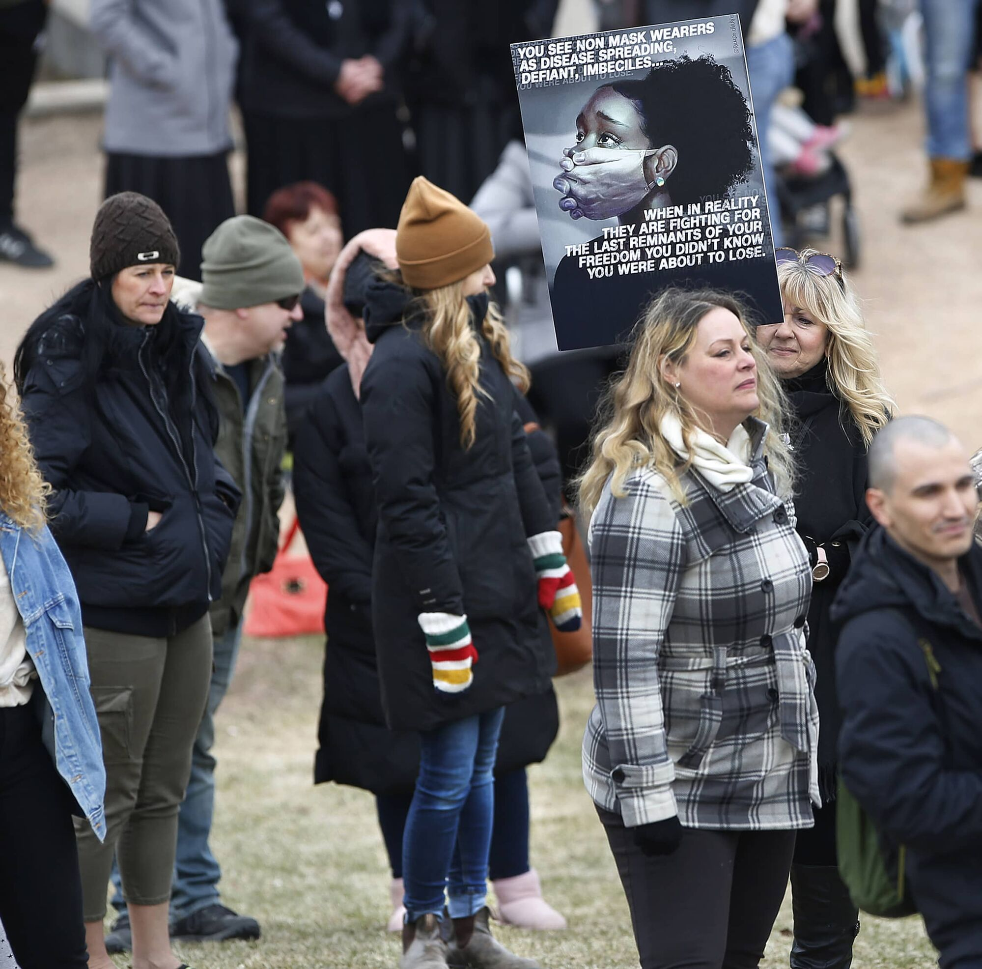 Hollie Buhler, seen at the rally in brown toque and striped mitts, who teaches Grade 1 at Elmwood School in Altona, has been suspended for attending the anti-mask rally in Winnipeg Sunday.  Parents raised concerns after seeing the photo that she might expose their children to COVID-19.