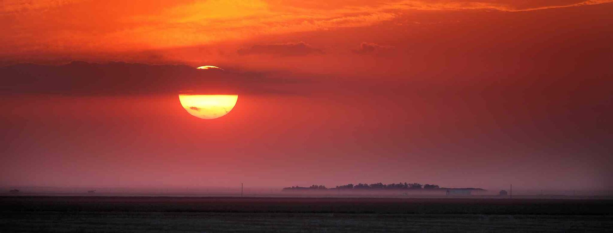 The sun eases into the western horizon, glowing red through the dust of the fall harvest in the Red River Valley.