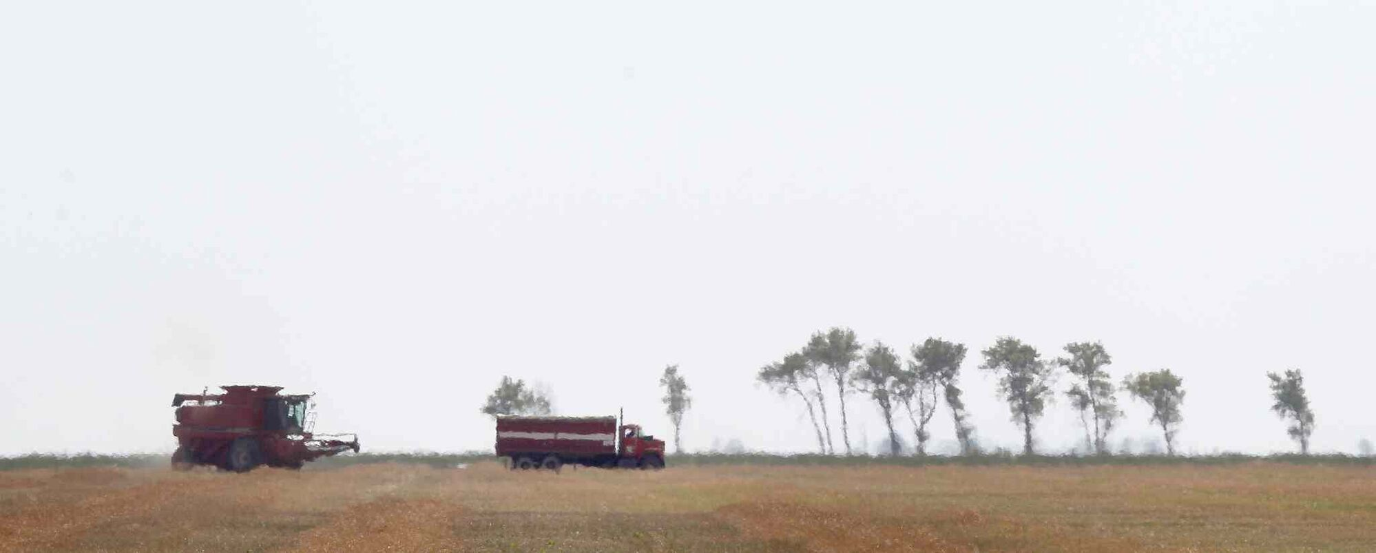 A combine and truck stand out against the sky near Sperling in late August. (Phil Hossack / Winnipeg Free Press)