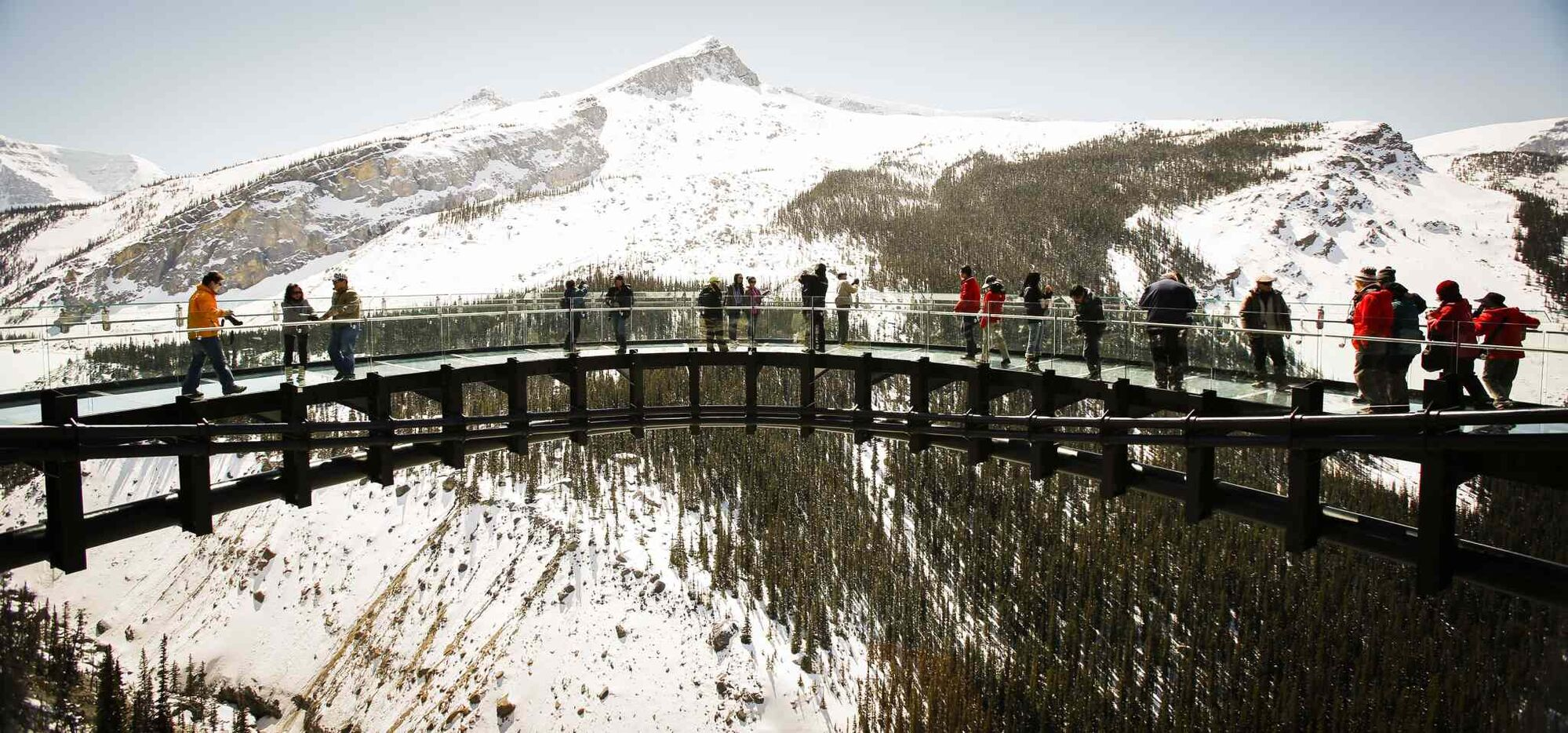 "Tourists take in the views from the newly opened Glacier SkyWalk near the Columbia Icefields in Alberta's Jasper National Park. Many environmentalists and residents of Jasper believe it is unnecessary and poses a risk to wildlife, particularly mountain goats and bighorn sheep. The Alberta Wilderness Association says it represents ""encroaching commercialization"" into the national parks. (Jeff McIntosh / The Canadian Press)"