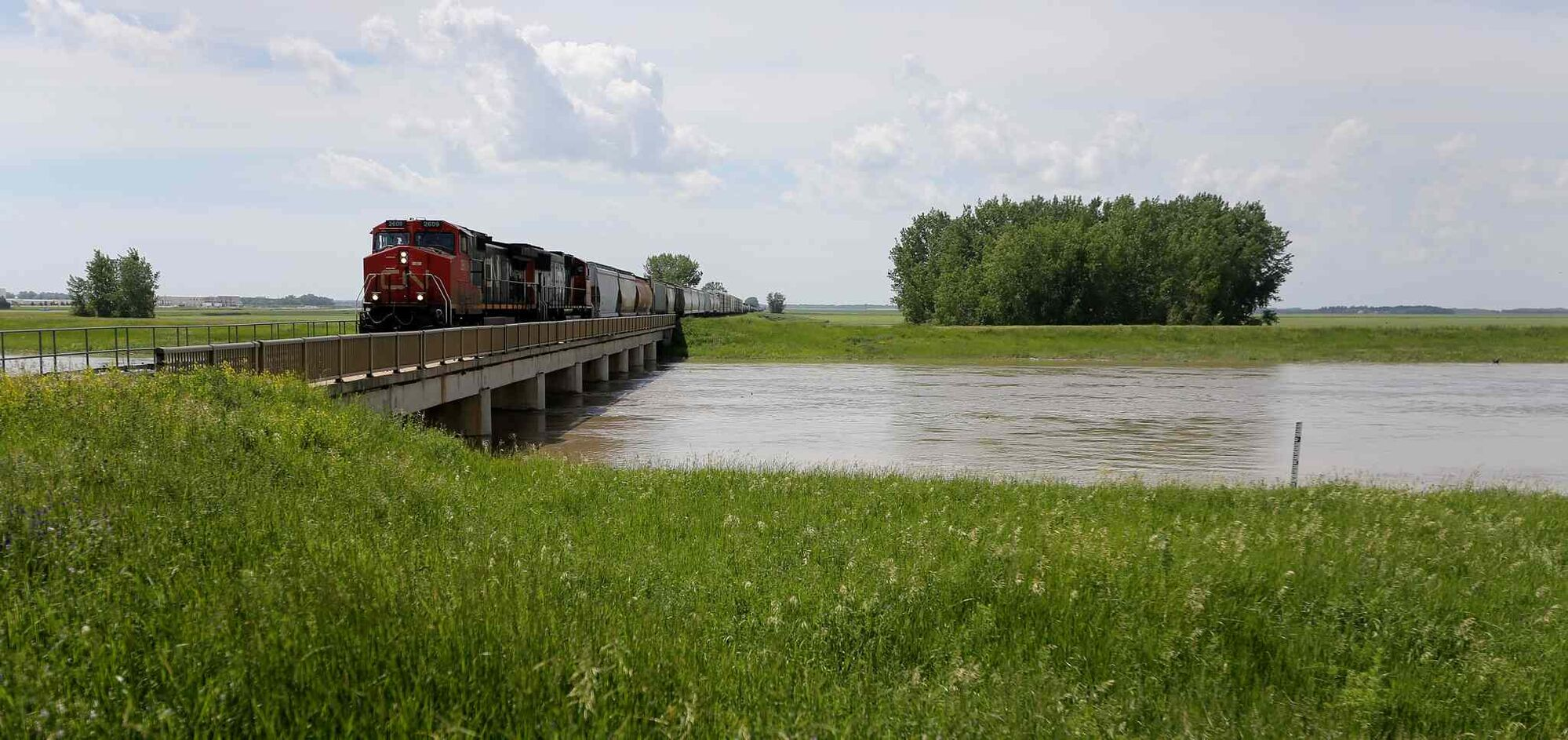 A CN Rail train crosses over the Portage Diversion near where construction workers strengthen the east side on Saturday, July 5. (TREVOR HAGAN/WINNIPEG FREE PRESS)