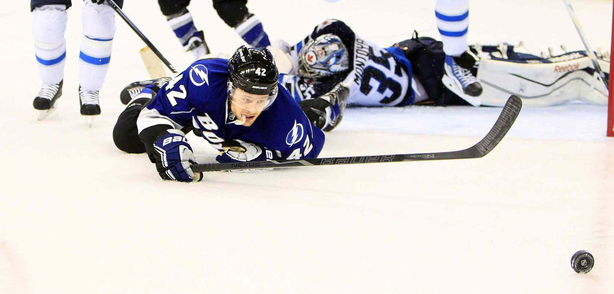 The Tampa Bay Lightning's Dana Tyrell (front) works to play the puck while down on the ice along with Winnipeg Jets goalie Al Montoya (right) during the first period. (Dirk Shadd / Tampa Bay Times / MCT)
