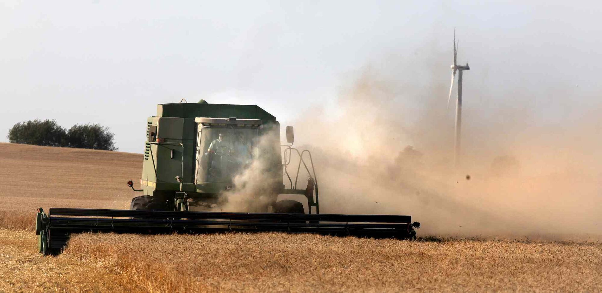A farm couple near Altamont share the cab of a combine harvesting a field of wheat.