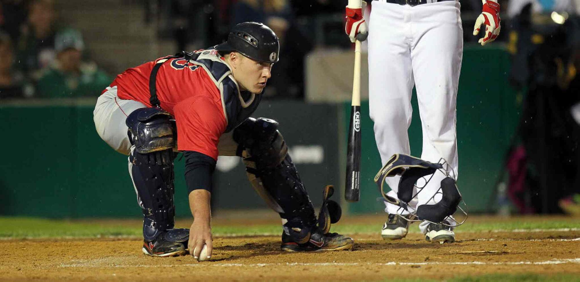 Lincoln Saltdogs' catcher Tyler Smith corrals a foul ball in the bottom of the third inning while keeping an eye on Goldeyes runners. (Phil Hossack / Winnipeg Free Press)