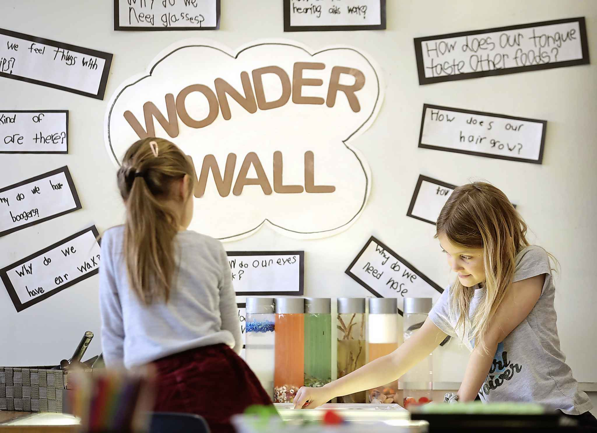 Janette Weiss (left) and Aubrie Wertepny work at the Wonder Wall in Kelly McLure's grade 1 class at Dawson Trail School.