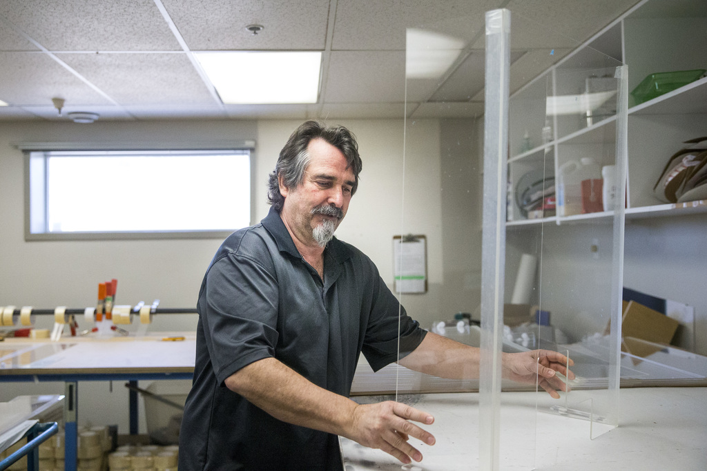 John Wardrope, owner of Acryl Design, opens up a freshly made cough guard in his Winnipeg shop on Monday. His company has made 2,500 in five days for retailers across Canada. (Mikaela MacKenzie / Winnipeg Free Press)