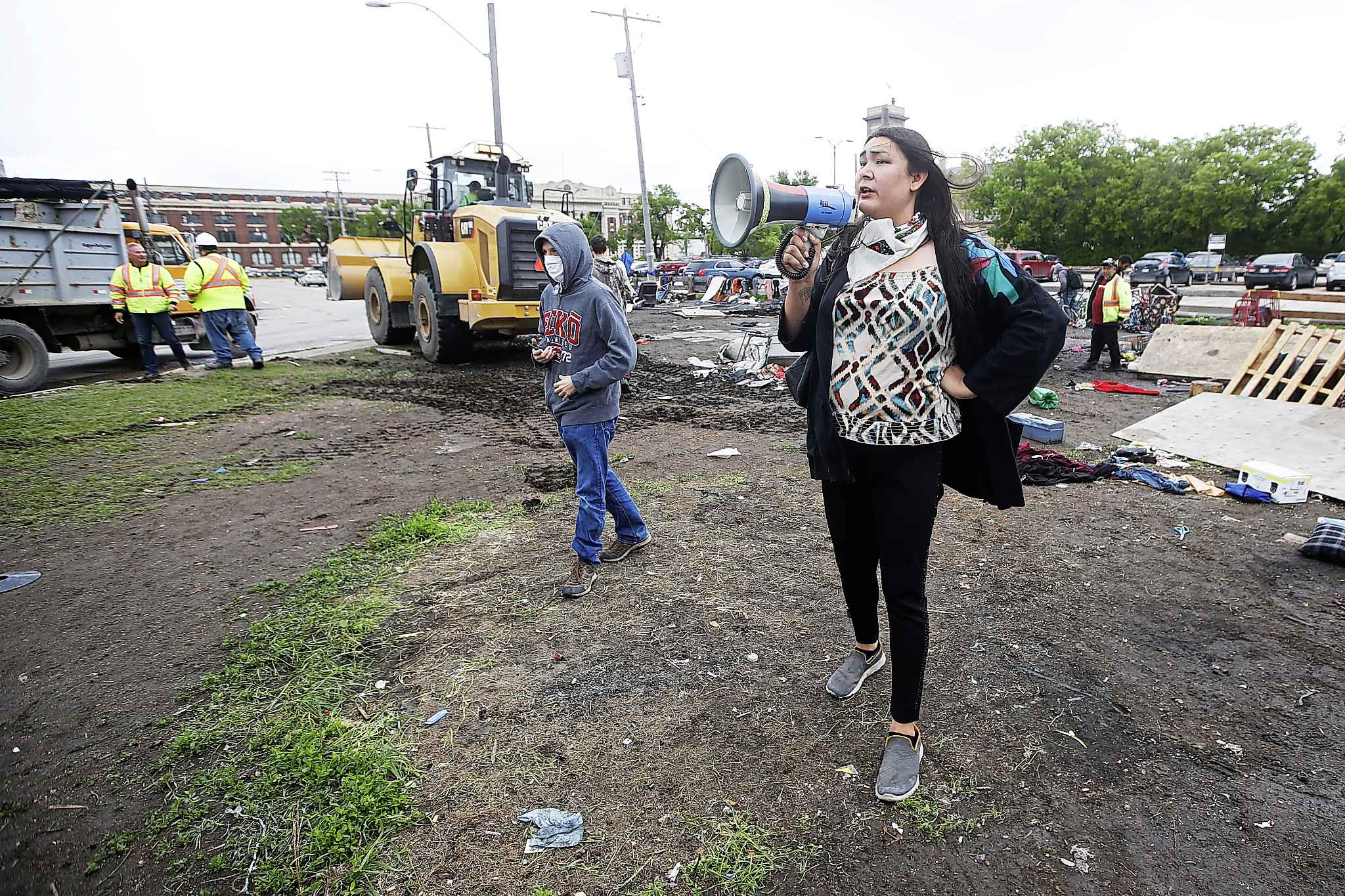 Protestors try to block city crews from dismantling camps on Austin Street and Henry Avenue on June 10.