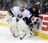 Islanders goalie Anders Nilsson squeezes out Winnipeg forward Blake Wheeler behind the net during second-period action Tuesday night.