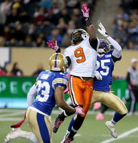 B.C. Lions' Ernest Jackson (9) catches a pass between Winnipeg Blue Bombers' Desia Dunn (23) and Bruce Johnson (25) during first half CFL football in Winnipeg Saturday.