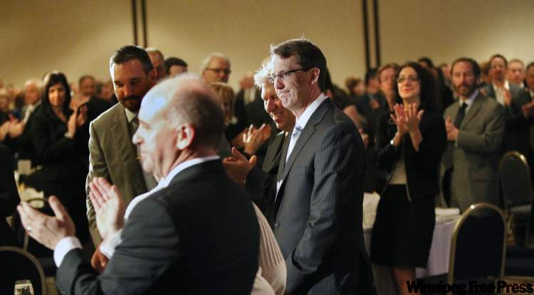 Mark Chipman (centre) receives a standing ovation as he arrives at the Winnipeg Chamber of Commerce luncheon on Thursday.