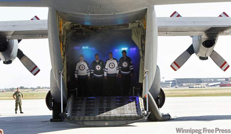 From left, Mark Stuart, Captain Andrew Ladd, Eric Fehr and Nik Antropov  emerge from a Hercules aircraft at a ceremony at 17 Wing Tuesday, where the Winnipeg Jets unveiled their dark home and white away jerseys.