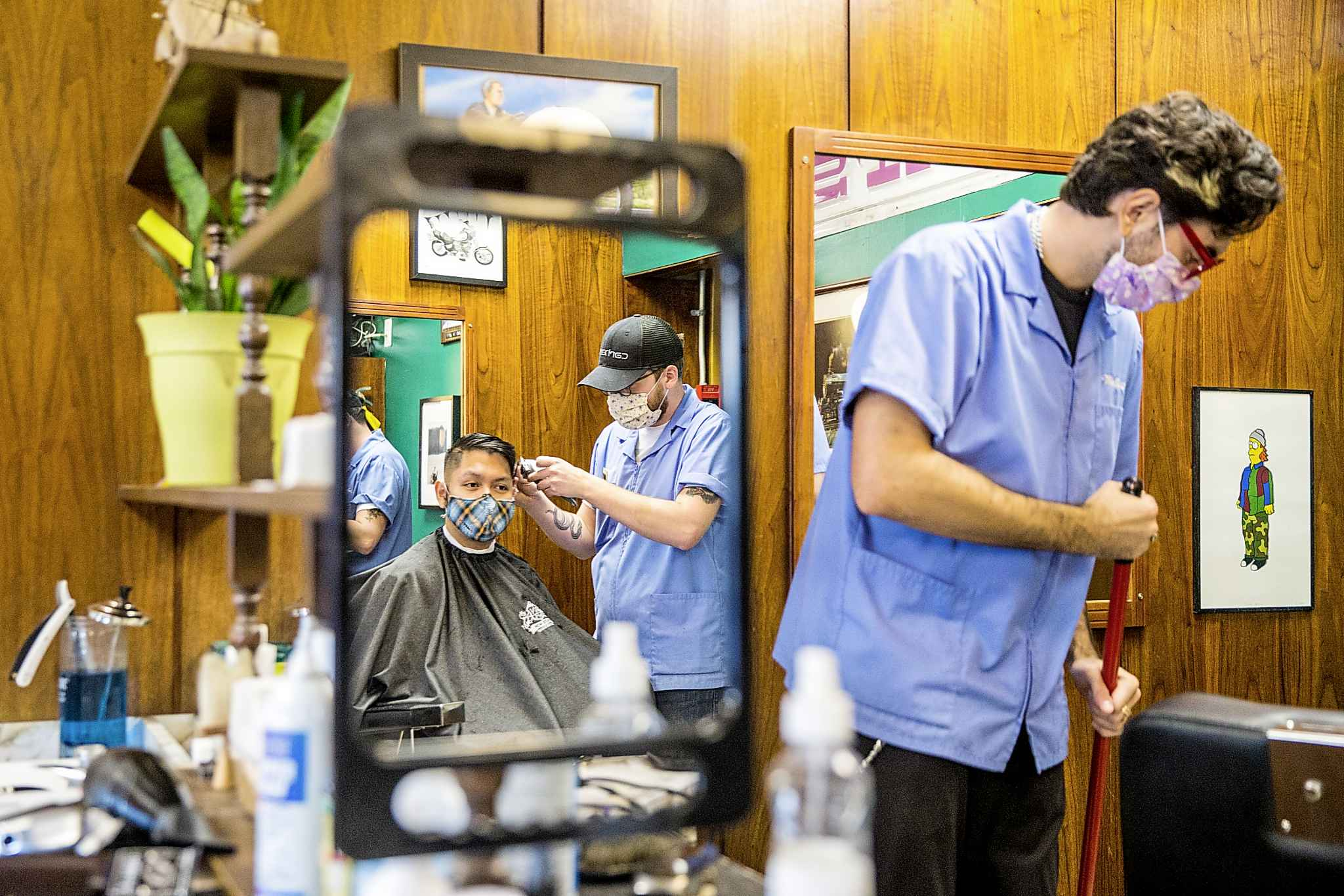 Ari Jakobson cuts Viet Bui's hair as Adam Woodbury sweeps up at Waltz On In barber shop, which will have to close on Thursday under new pandemic restrictions. (Mikaela MacKenzie / Winnipeg Free Press)