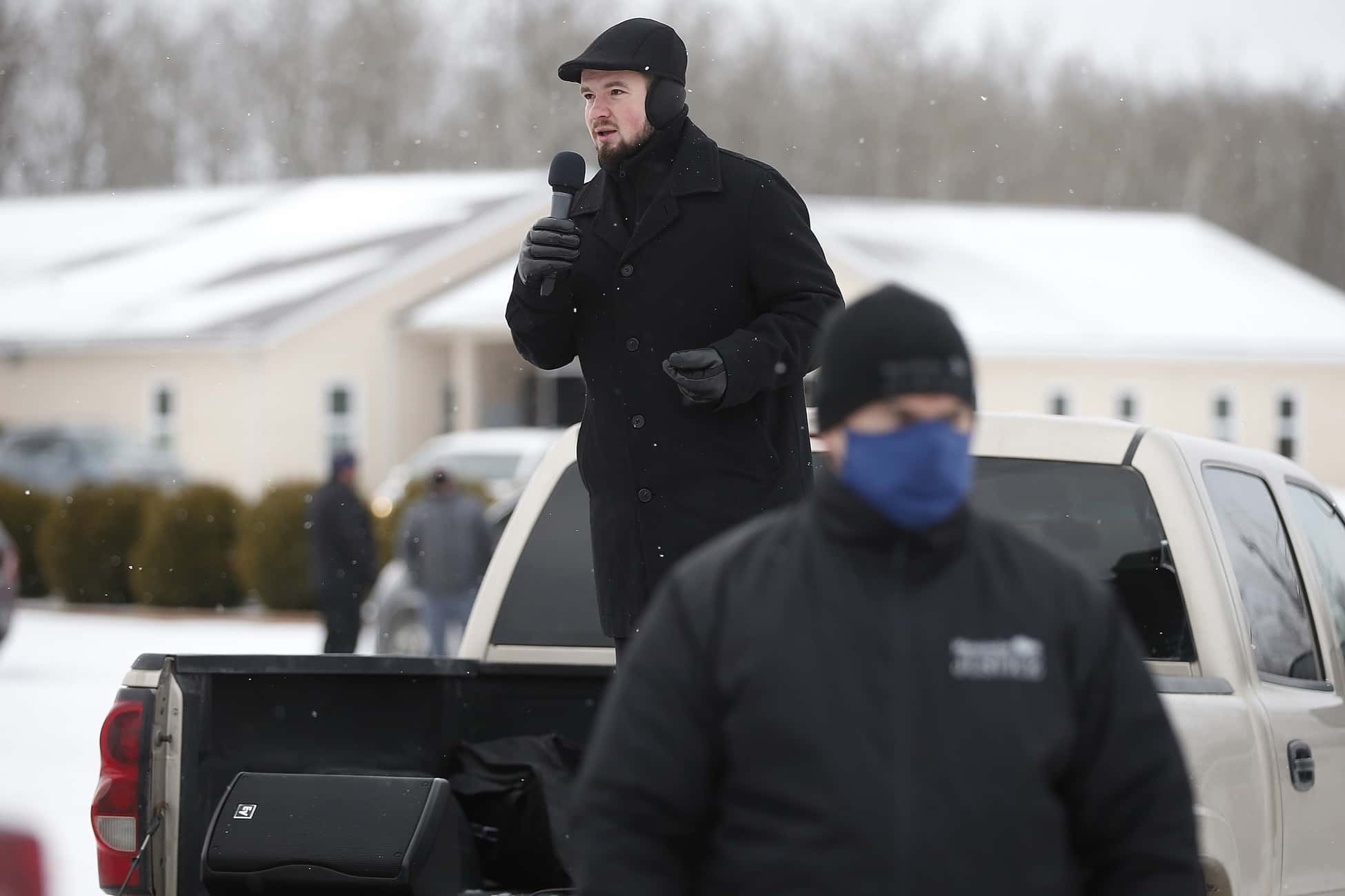 Tobias Tissen, minister at the Church of God Restoration, spoke from the back of a pickup truck as RCMP officers and Manitoba Justice officials blocked the entrance to The Church of God Restoration, just south of Steinbach on Sunday morning. Under the current public health restrictions, all faith-based gatherings must be held virtually. (John Woods / Winnipeg Free Press)