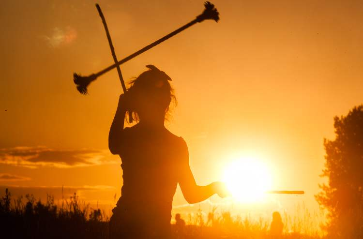 A festival-goer plays with devil sticks as the sun sets. (Melissa Tait / Winnipeg Free Press)