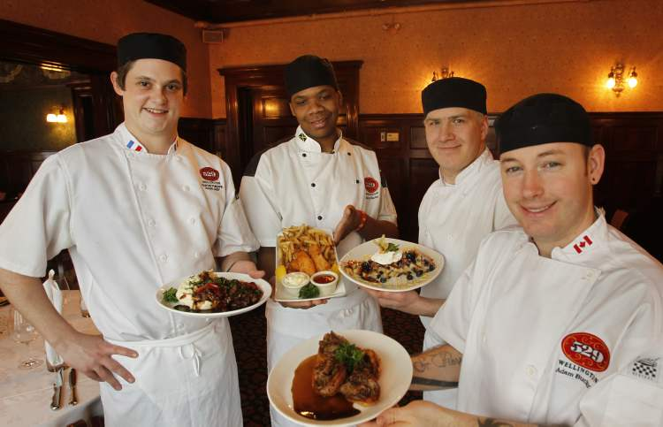 From left, 529 Wellington's sous-chef Martin Philippe with sauteed beef tenderloin, first cook Delroy Clarke with fried pickerel and chips, sous chef Thomas Revoy with blueberry bread pudding for two and first cook Adam Buchan with mini-Yorkshires stuffed with prime rib.