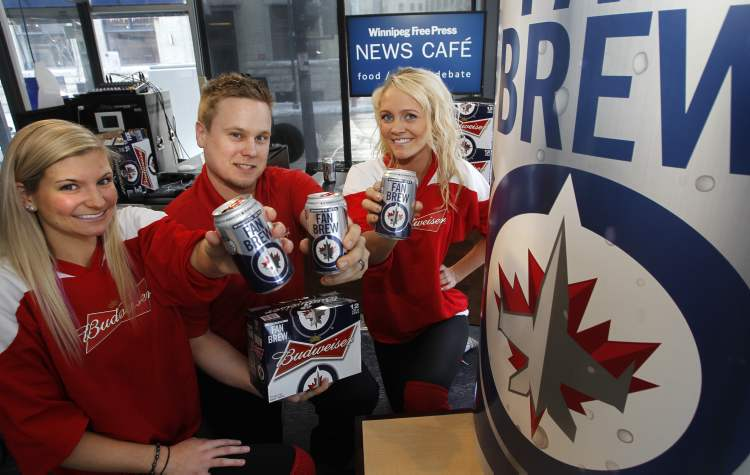 Dan Chubey is flanked by Bud reps (left) Lauren Shepherd and Brittany Christiansen with cans of the new Winnipeg Jets fan brew.