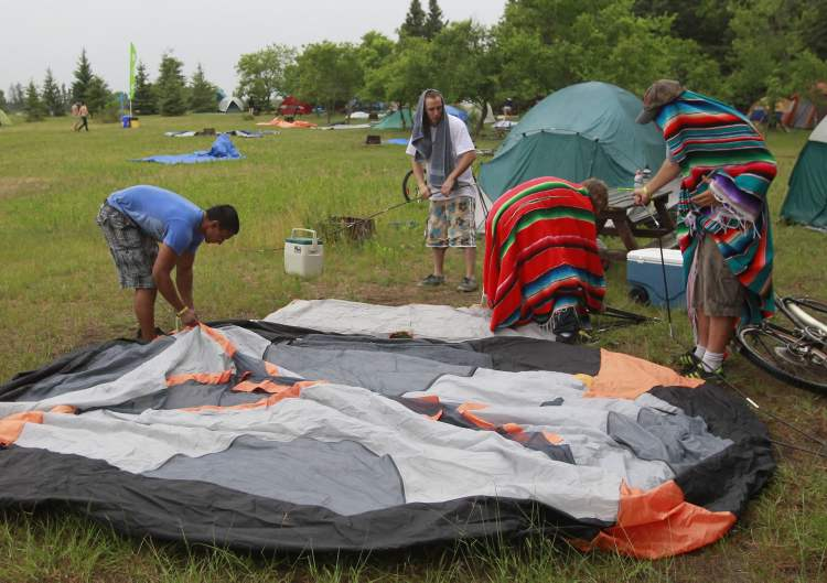 Folk Festival campers set up their tent in the campground in the rain Wednesday. (Wayne Glowacki / Winnipeg Free Press)