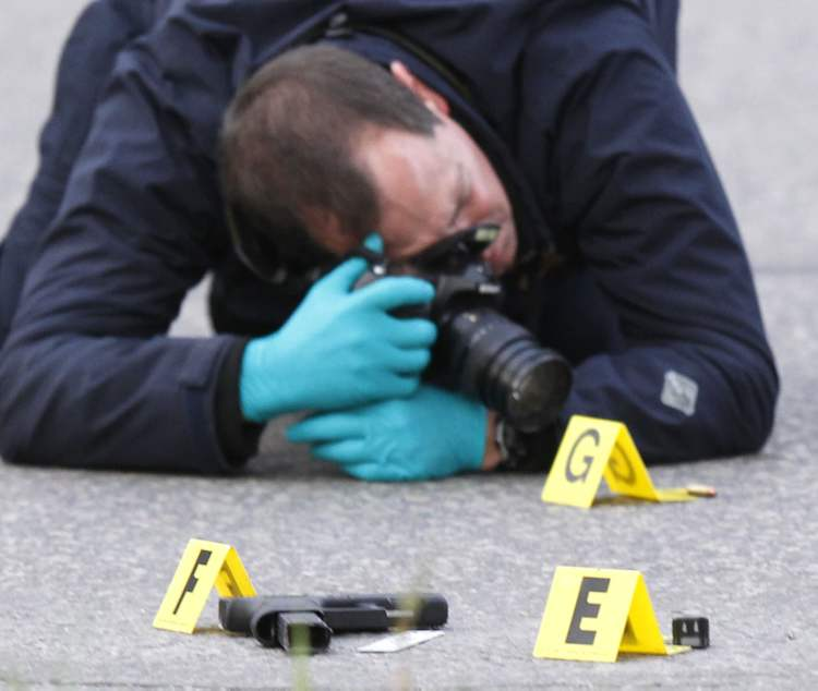 A police officer photographs bullet and a handgun on Stafford Street at Hector Avenue.
