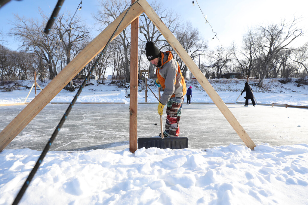 Ted Geddert shovels snow off the rink he made on the Red River near Fraser Grove Park for his family and area residents to enjoy. (Ruth Bonneville / Winnipeg Free Press)