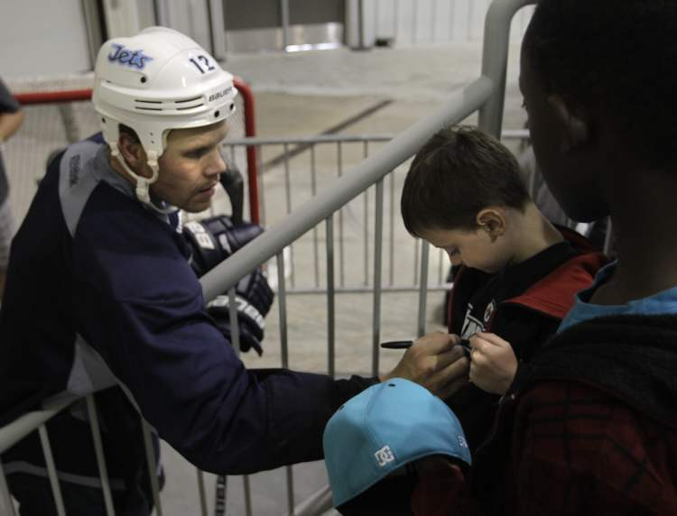 Olli Jokinen signs the shirt of five-year-old Eric Nanka. (Wayne Glowacki / Winnipeg Free Press)
