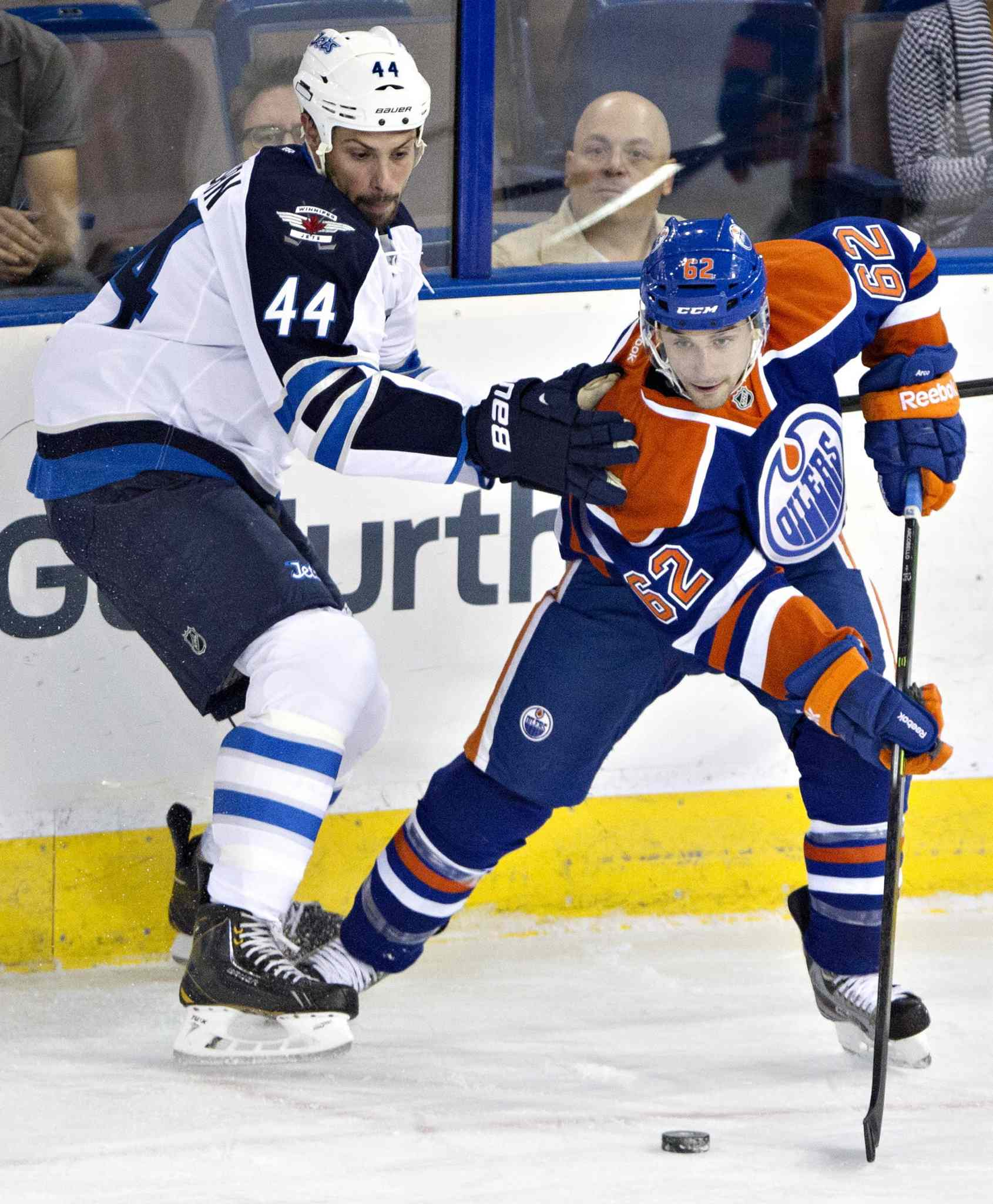 Winnipeg Jets Zach Bogosian (left) and Edmonton Oilers Mark Arcobello (right) battle for the puck in the corner during the first period.