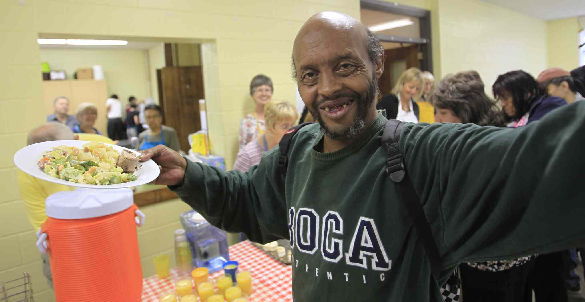 The congregation may be gone, but Trinity Lutheran Church is still a popular meeting place. On a recent Friday at the building, Simba gets a hot lunch provided by Secret Place Ministry.
