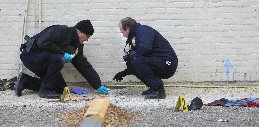 Police forensic officers investigate the scene a fatal fall Tuesday morning.