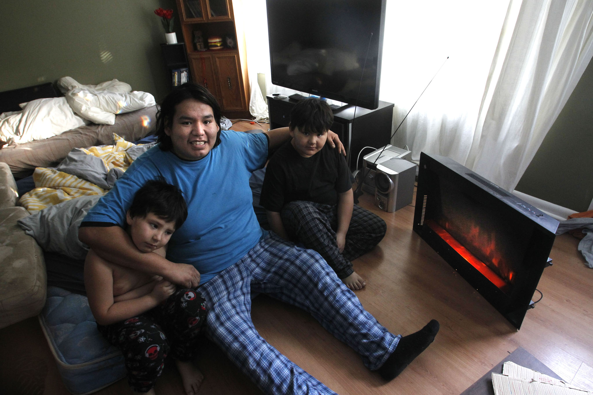 Derek Dowan and his two sons Dave,6 (left) and Daniel, 9, keep toasty warm Monday morning by the electric heater and heat from the kitchen stove in their Niverville home.