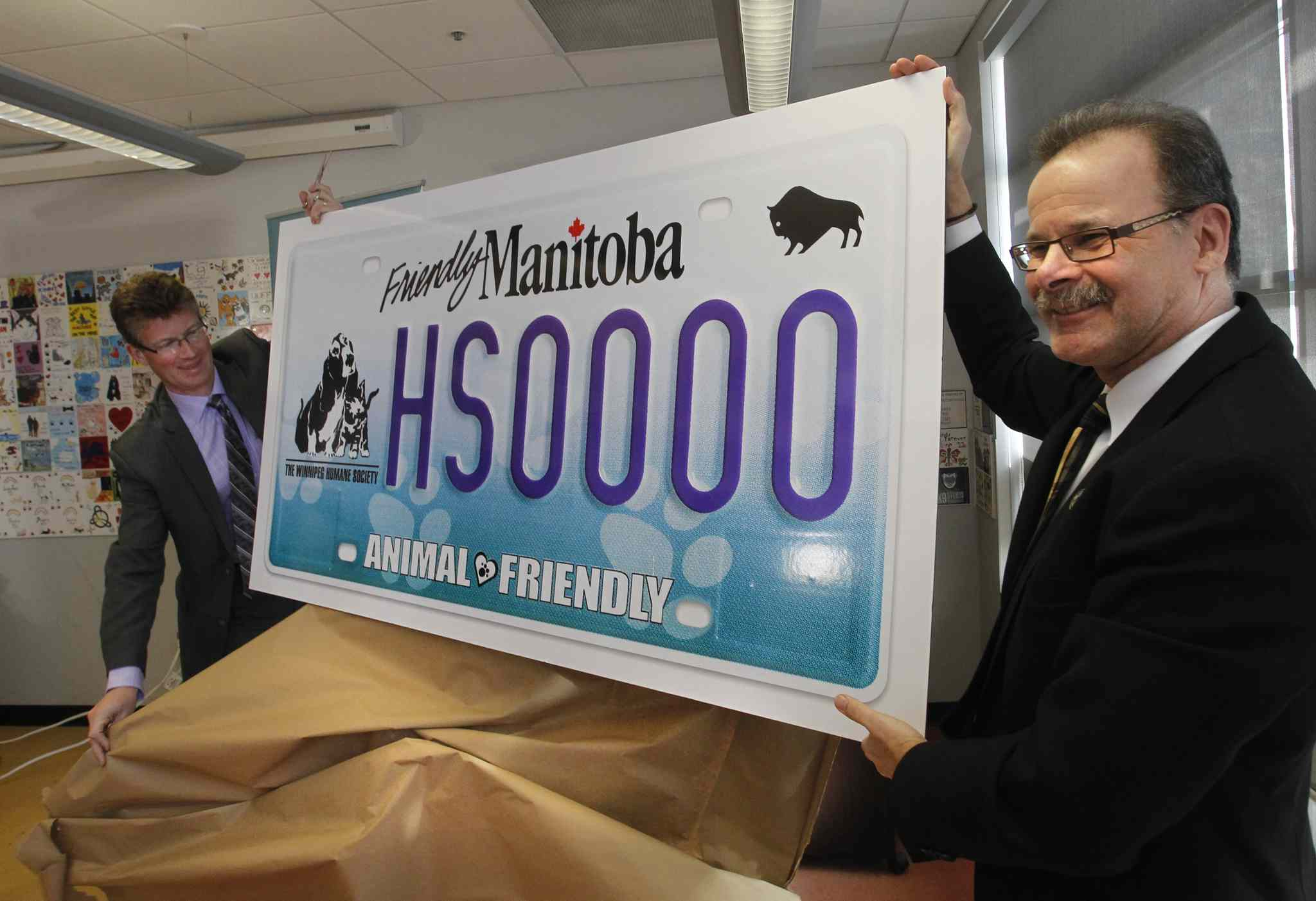 At right, Bill McDonald, CEO of the Winnipeg Humane Society and Justice Minister Andrew Swan unveil the new Winnipeg Humane Society specialty licence plate this afternoon.